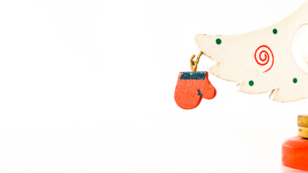 Christmas white ticket decorated with a wooden red glove hanging on a branch of a wooden toy Christmas tree