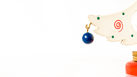 Christmas white ticket decorated with a wooden blue ball hanging on a branch of a wooden toy Christmas tree