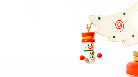 Christmas white ticket decorated with a wooden snow puppet whit a red hat hanging on a branch of a wooden toy Christmas tree