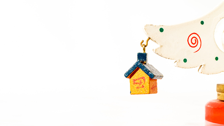 Christmas white ticket decorated with a wooden yellow house with a blue roof hanging on a branch of a wooden toy Christmas tree