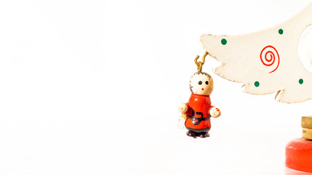 Christmas white ticket decorated with a wooden child hanging on a branch of a wooden toy Christmas tree
