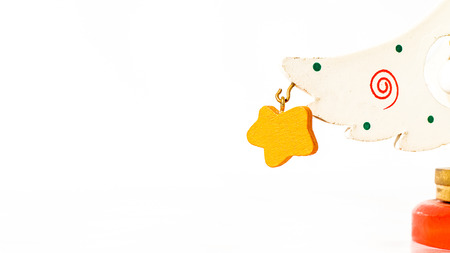 Christmas white ticket decorated with a wooden yellow star hanging on a branch of a wooden toy Christmas tree