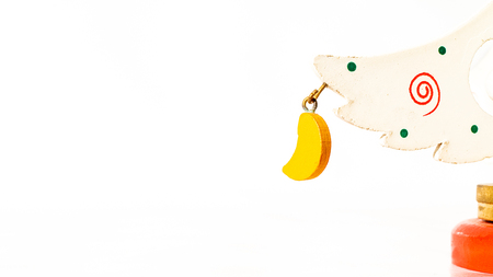 Christmas white ticket decorated with a wooden yellow moon hanging on a branch of a wooden toy Christmas tree