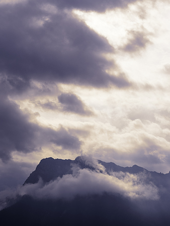 Silhouette of mountain ridge hurling itself in a cloudy sky
