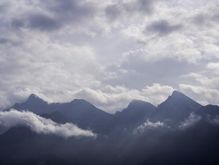 Mountain range silhouette that break in an half in cloudy sky Banco de Imagens
