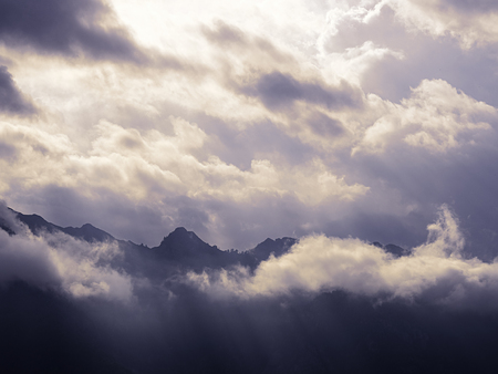Mountain peaks silhouette that break a cold cloudy sky