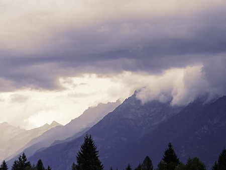 Mountains chain with color degrade, topped by clouds with pines in foreground Banco de Imagens