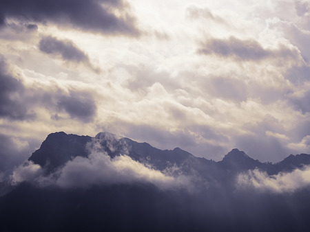 Silhouette of mountain ridge that break a cloudy sky