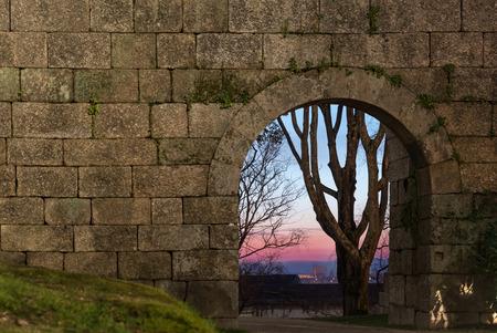 antigua puerta de arco de piedra en una pared y un árbol lejos al atardecer Foto de archivo