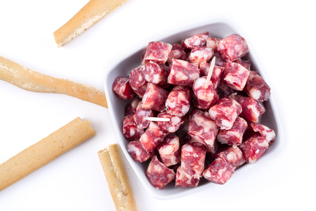 dry sausage: delicious dry sausage cutted in small pieces in a bowl and bread sticks