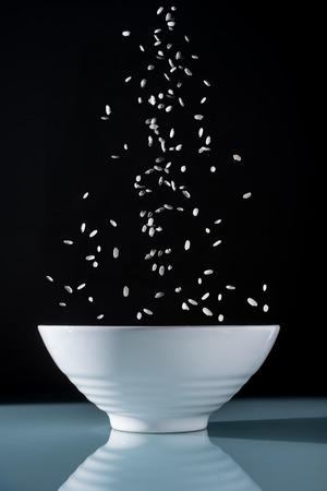 rice falling in a white oriental bowl