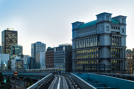 Tokyo monorail at dusk with buildings and train