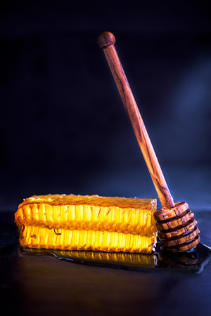 wax honeycomb backlit and honey in a dark food background and wooden spoon