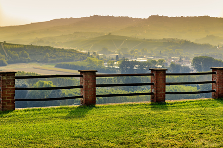 cavour: Langhe hills and fence during golden hour as seen from Grinzane Cavour Castle park in Italy