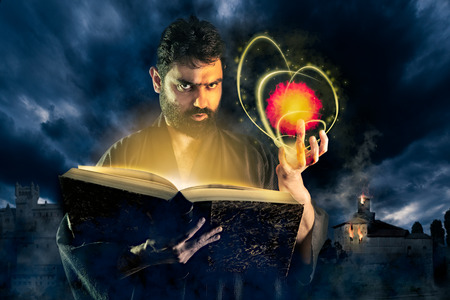 Male sorcerer casting a fireball spell from a magic book as halloween image
