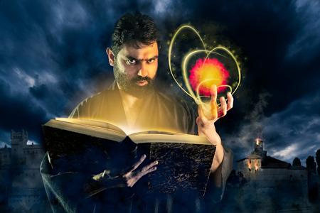 fireball: Male sorcerer casting a fireball spell from a magic book as halloween image
