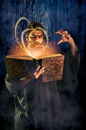 ハロウィン イメージとして魔法の本から呪文をかけた男性の魔術師 写真素材 - 64390970
