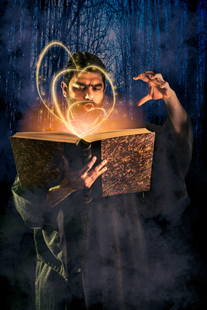 Male sorcerer casting a spell from a magical book as halloween image
