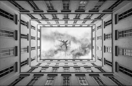 Jet airplane passing on cluod sky in a big city Lizenzfreie Bilder