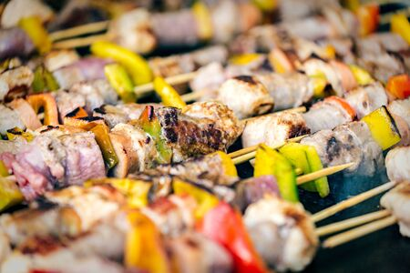 grilled skewers of different meat and vegetables on a hot grill Lizenzfreie Bilder