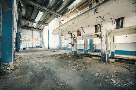 Interior of abandoned industry with dirt and rusty thinghs, broken bricks