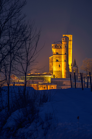 Serralunga castle during a cold winter night with snow in langhe region, Italy,vertical