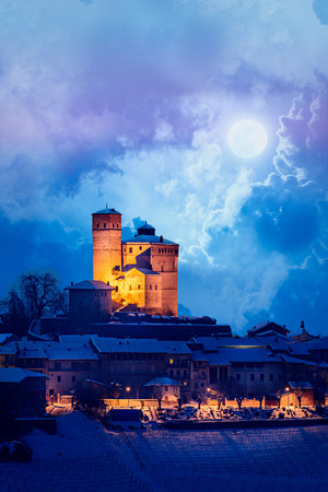 Serralunga castle during a winter night with moon and snow in langhe region, Italy Standard-Bild