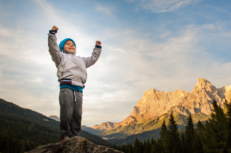 a child conquers the summit, loose his proud arms, in the background the Alps