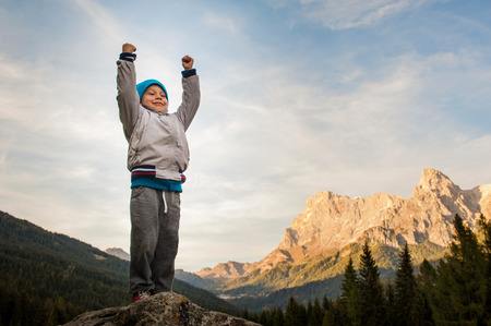 scaling: a child conquers the summit, loose his proud arms, in the background the Alps