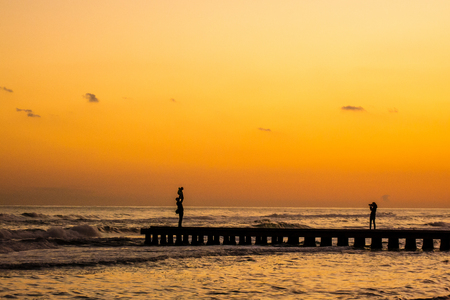 a woman photographs a dad that raises her son in the air, the scene is a silhouette takes place at sunset on a dock at the sea Stock Photo