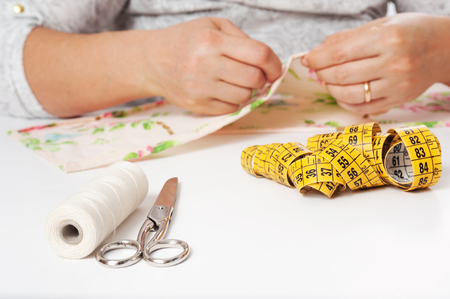 hands of young woman sewing