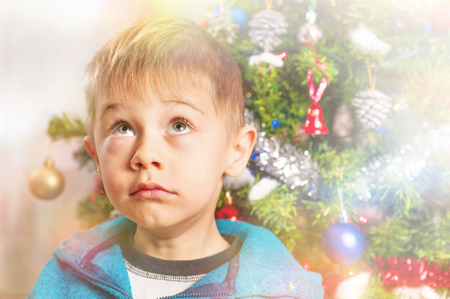 baby awaits Santa Claus with doubtful expression, seems to wonder: does it really exist? 版權商用圖片