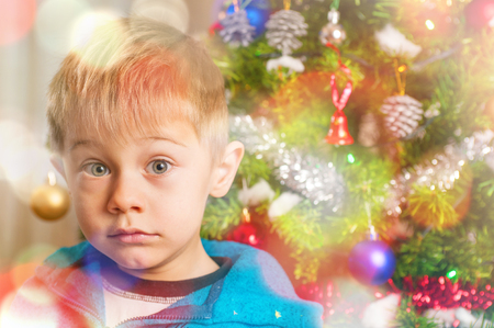 baby awaits Santa Claus with doubtful expression, seems to wonder: does it really exist? Stock Photo