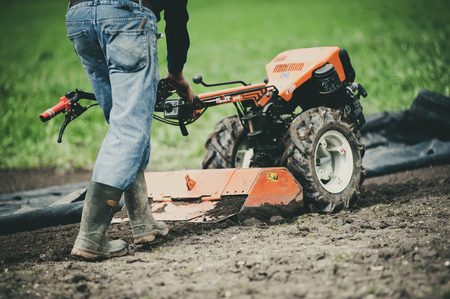 farmer with motor cultivator prepares the ground in spring