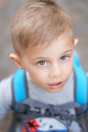 blond child looks in camera from bottom to top