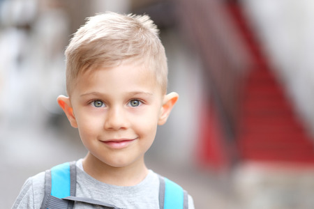 blond child looks in camera and smiles
