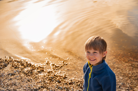blond child smiles by the lake at sunset