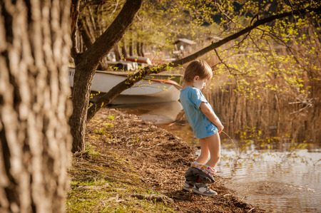 blond child pee in the lake Stock Photo