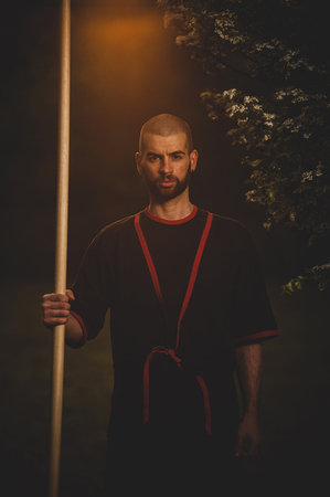 martial arts fighter Wing Tsun, Caucasian with kimono and long stick in the sunset