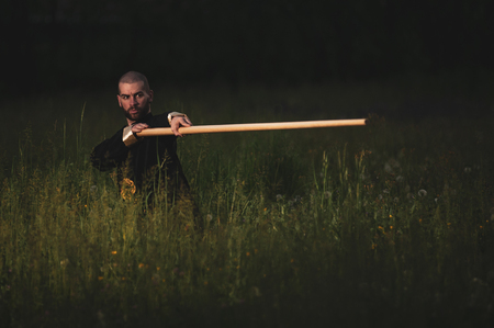 martial arts fighter Wing Tsun, Caucasian with kimono and long stick in the tall grass