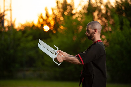martial arts fighter Wing Tsun, Caucasian with kimono and double knife in sunset Zdjęcie Seryjne