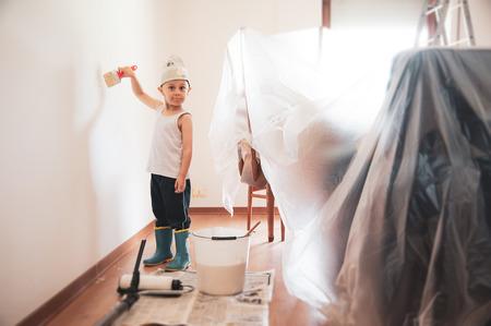 child painter paints walls with paper hat
