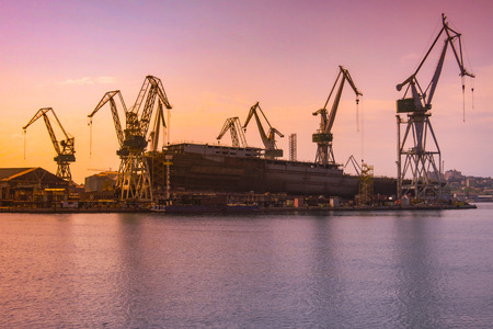shipyard with large ship under construction at the sunset