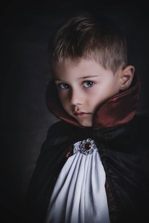 charming baby dressed as a vampire in a dark atmosphere, with gothic  and elegance clothes