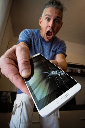 a man exclaims for having cracked the screen of the smartphone, phone in the foreground, a slightly blurred man in the background Banco de Imagens