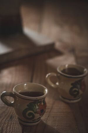 two antique coffee cups decorated on a wooden background in a quiet and intimate atmosphere Zdjęcie Seryjne