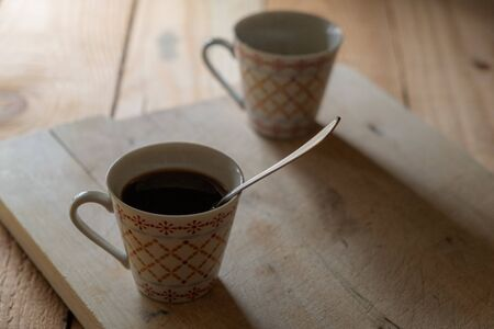 two cups of coffee on a wooden cutting board in a quiet and rustic atmosphere
