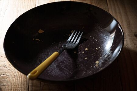 empty plate dirty with crumbs with a yellow fork in a quiet and dark atmosphere Zdjęcie Seryjne