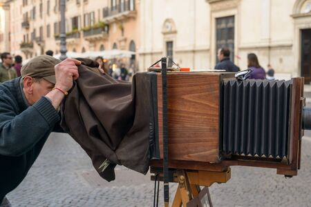 Rome, Italy - March 28, 2015: a man takes pictures to tourists with an old camera in Navona square