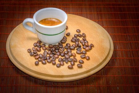 cofe: A cup of coffee on wood with seeds around